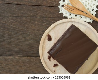 Chocolate cake on a plate on a wooden table.