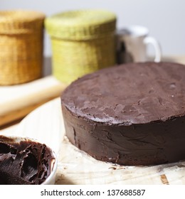 A chocolate cake on the table with a kneader, a chocolate bowl and other baking equipment. Square format./ Chocolate cake