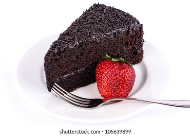 Chocolate cake on the table with strawberries and chocolate.