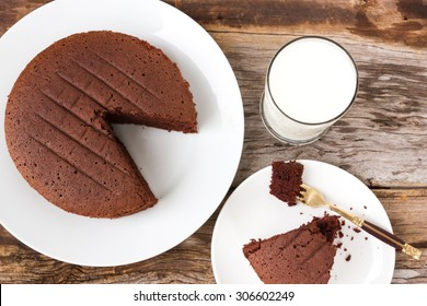 Chocolate cake on white plate with a glass of milk over wooden table. Selected focus on a glass of milk.