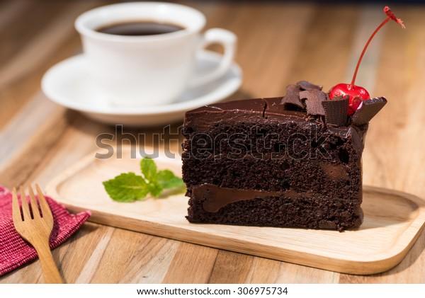 コーヒーカップの入った木のテーブルの上にチョコレートケーキ