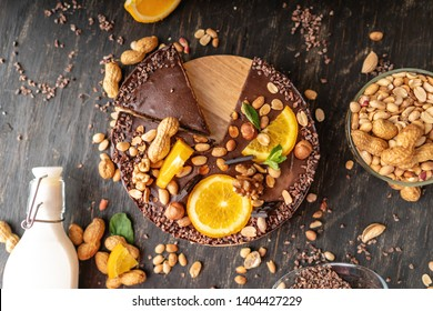 Chocolate cake with orange, cacao, mint leaves, peanuts and nuts. Top view. Concept healthy raw gluten-free and milk-and flour-free desserts for vegan food