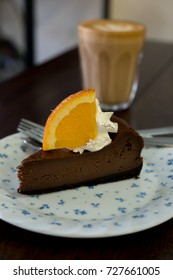 Chocolate cake with orange and latte coffee on wood table