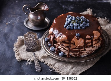 Chocolate cake from chocolate pancakes with icing, with blueberries.Vintage style.selective focus.
