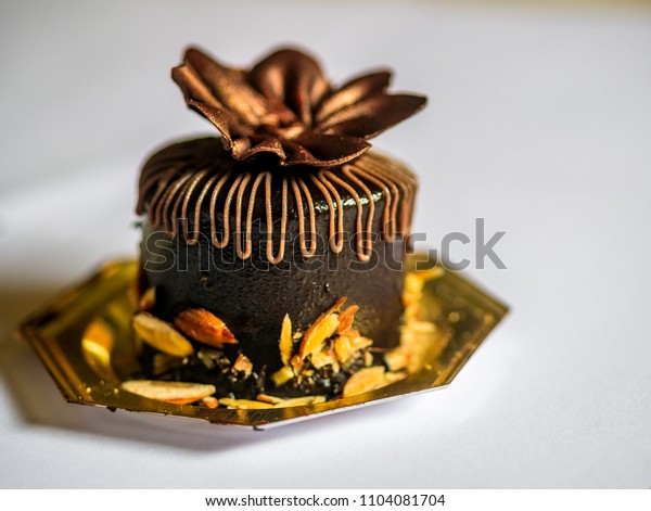 Chocolate cake pastry with chocolate cream and fresh chopped almonds on plate, with white background