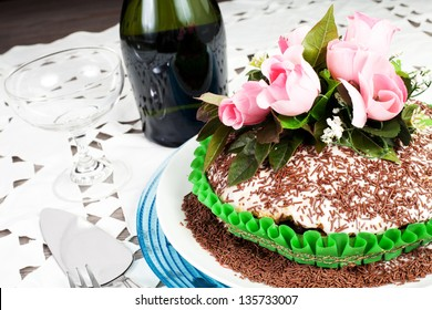 chocolate cake with pink rose on the wood table with champagne