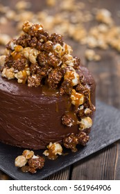 Chocolate cake with popcorn on wooden table.
