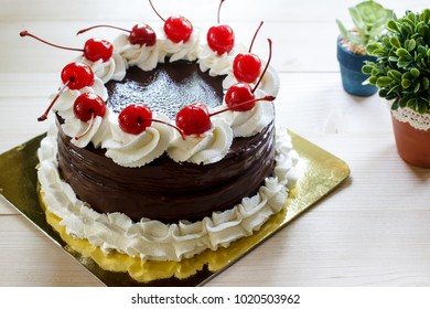 Chocolate cake with red cherry and whipping crea.