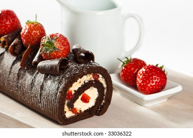 Chocolate cake with strawberries and cream on wooden board