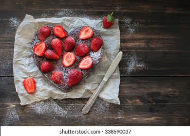 chocolate cake with strawberries on a paper on dark desk