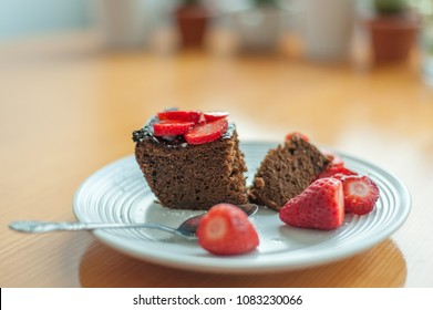Chocolate cake and strawberries on wooden table