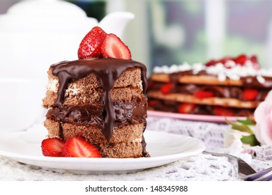 Chocolate cake with strawberry on wooden table on room background