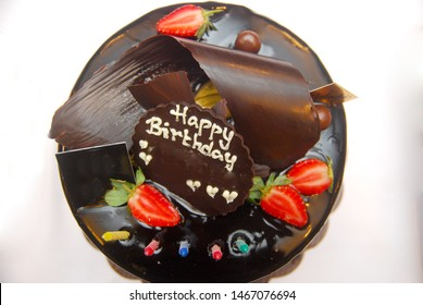 chocolate cake with strawberry slices, and chocolate with a happy birthday greeting. From top view on white background