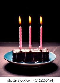 Chocolate cake with three pink candles on blue plate, black background