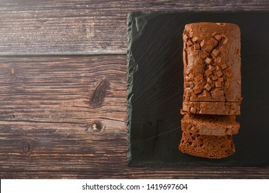 Chocolate cake. Top view of pound cake with chocolate chips, wooden board.
