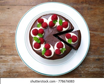 chocolate cake topping with chocolate ganache ,raspberry and whipped cream