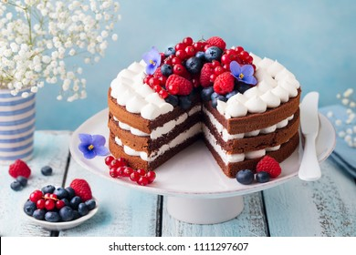 Chocolate cake with whipped cream and fresh berries. Blue wooden background.