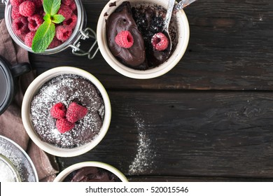 Chocolate cakes with berries on the dark wooden background with copy space, top view