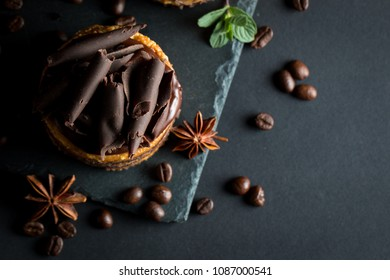 Chocolate cakes on black slatter board with mint, coffee beans on dark background, closeup photo. Fresh, tasty dessert food concept.