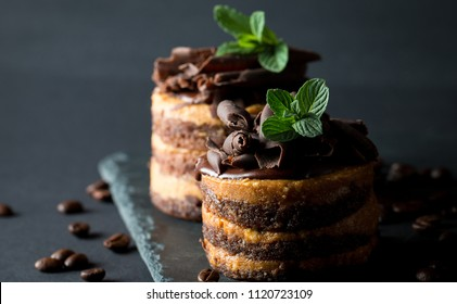Chocolate cakes on black slatter board with mint, coffee beans on dark background, closeup photo. Fresh, tasty dessert food concept.