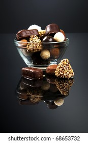 Chocolate candies assortment in glass bowl on black background