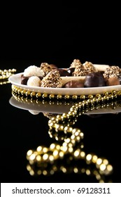 Chocolate candies assortment on white plate with golden jewelry. Macro shot on black background