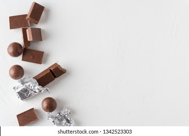 Chocolate candies and bitten chocolate bars on white textured background. Trendy  flat lay style. Place for text.