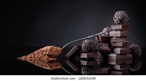 Chocolate candies, broken chocolate pieces and spoon with cocoa powder on a black reflective background.