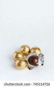 Chocolate candies in the foil on a white background