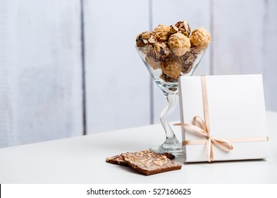 Chocolate candies in glass and box over white background.