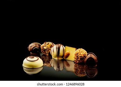 Chocolate candies on a black mirror surface sprinkled with coconut chips and hazelnut, dark chokolate candy. Sweet time menu