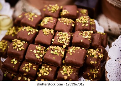 Chocolate candies with pistachios topping on the table.