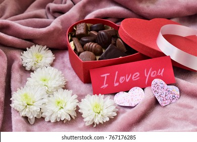 Chocolate candies in the red heart shaped box , white natural flowers and love note, Valentine's Day romantic present, sweets and romance.