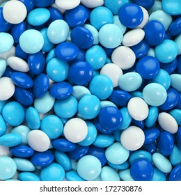 Chocolate candy coated in blue and white. Background