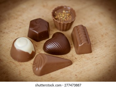 Chocolate candy in the shape of heart among other on wooden background