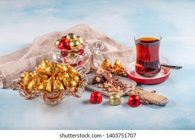Chocolate candy in shiny wrapper. Delicious chocolate candies and tea on wooden background. Ramadan Eid (Ramadan feast) Concept.