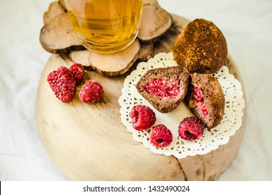 Chocolate candy truffle with raspberry on a wooden stand with glass of green tea. Close-up.