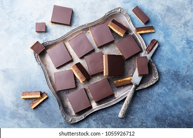 Chocolate caramel slices, bars,  millionaires shortbread on a vintage tray. Blue background. Top view.