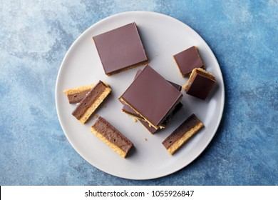 Chocolate caramel slices, bars,  millionaires shortbread on a grey plate. Blue background. Top view.