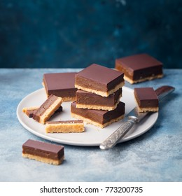 Chocolate caramel slices, bars,  millionaires shortbread on a grey plate. Blue background.