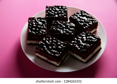 Chocolate cheese cake with blackcurrant or bluberry filling / topping on a round plate. Close-up of sweet dessert against pink / magenta background. Delicious food for holiday dinner,