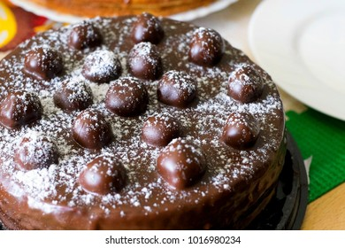 Chocolate cherries cream cake. Close-up chocolate cake with sugar icing & cherry decoration. Chocolate cherries cake on party celebration dinner table background. Pie with berries covered cocoa glaze