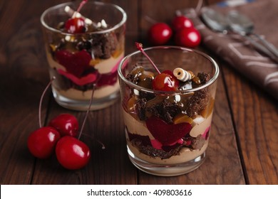 Chocolate and cherry dessert in glass on dark wooden background. Shallow focus