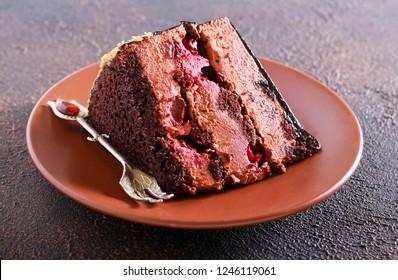 Chocolate cherry layered cake slice on plate