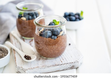 Chocolate chia pudding with blueberry, almonds and mint on top in a glass jar on a white wooden background. Healthy food. Copy space