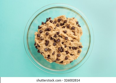 Chocolate chip cookie dough in a glass bowl on a blue table cloth.