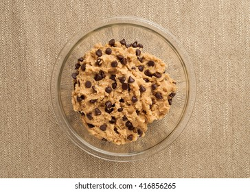 Chocolate chip cookie dough in a glass bowl on a textured brown table cloth.