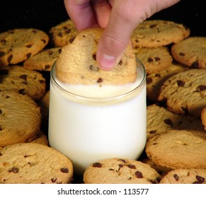 A chocolate chip cookie dunked into a glass of milk