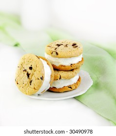 Chocolate chip cookie and ice cream sandwiches on green and white background.