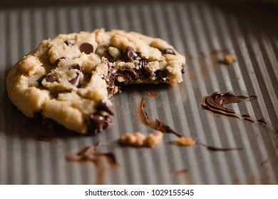 Chocolate chip cookie isolated on a cookie sheet with melted chocolate.